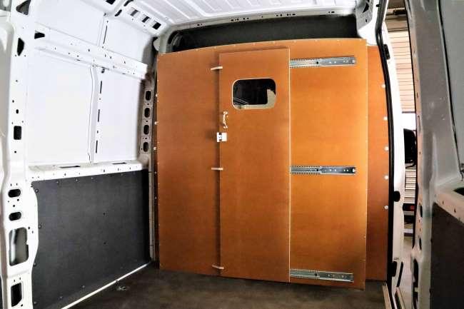 Tussenschot met schuifdeur vervaardigd van Berken multiplex om te plaatsen tussen cabine en laadruimte. Dit voorkomt dat materiaal bij remmen naar voren vliegt. Daarnaast vermindert het rijgeluid en heb je meer profijt van de verwarming en de airco